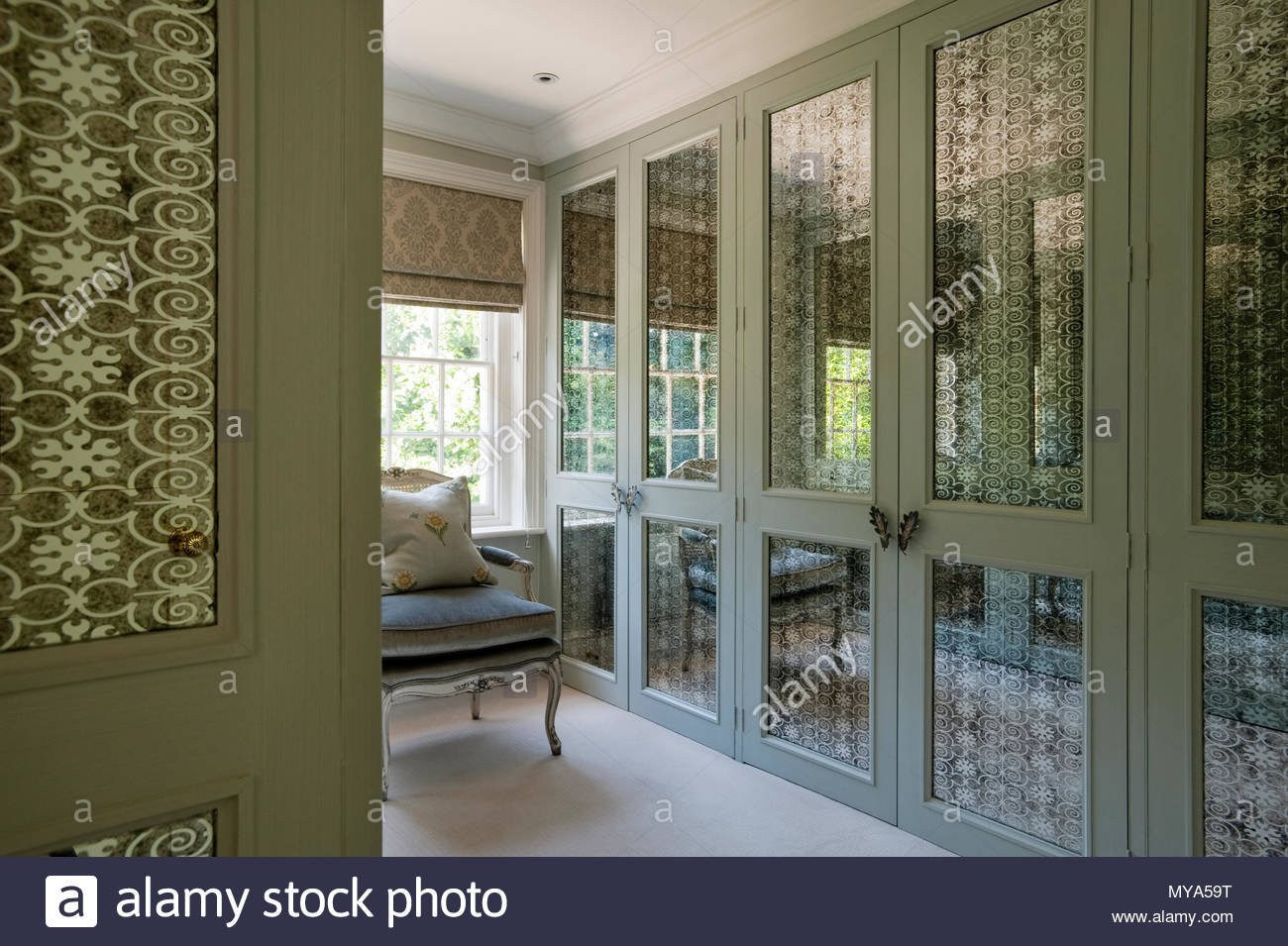Elegant armchair and wardrobes - Stock Image
