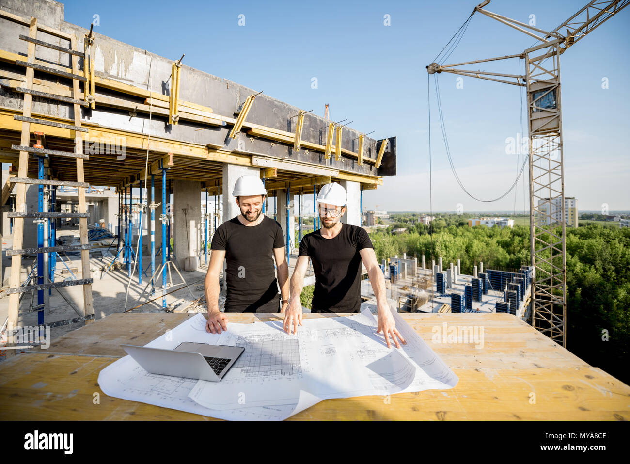 Workers with drawings at the construction site - Stock Image