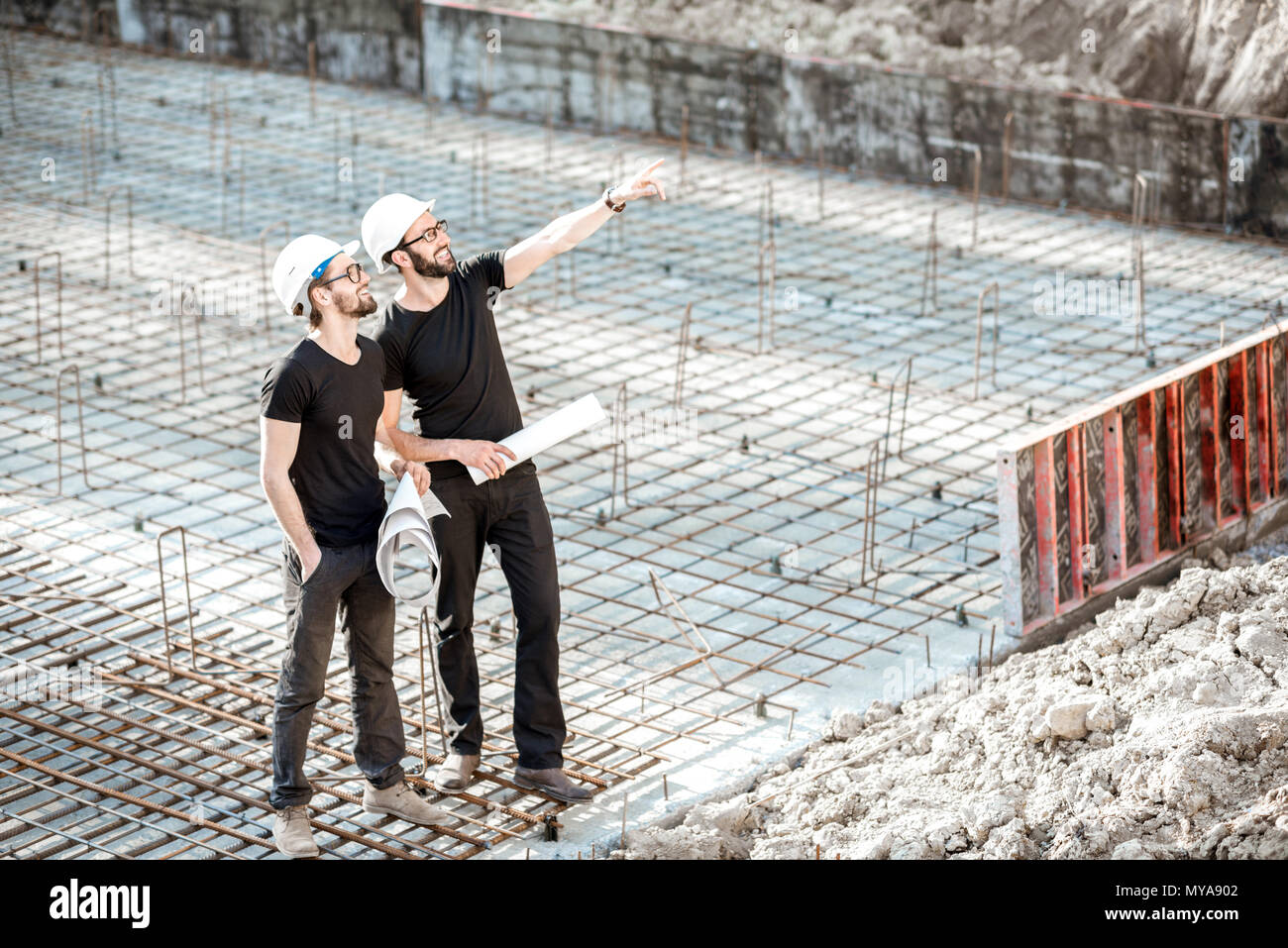 Builders with drawings at the construction site - Stock Image