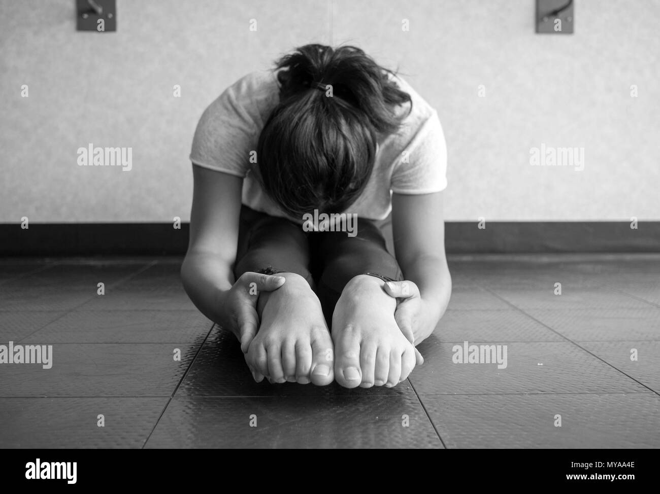 Black and white version of Young woman performing and sit and reach to stretch hamstrings and increase flexibility - Stock Image