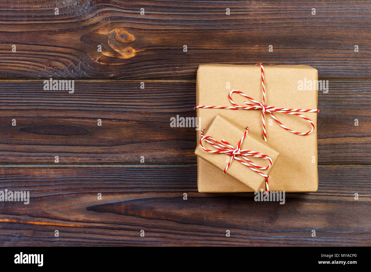 Christmas presents laid on a wooden table background. - Stock Image