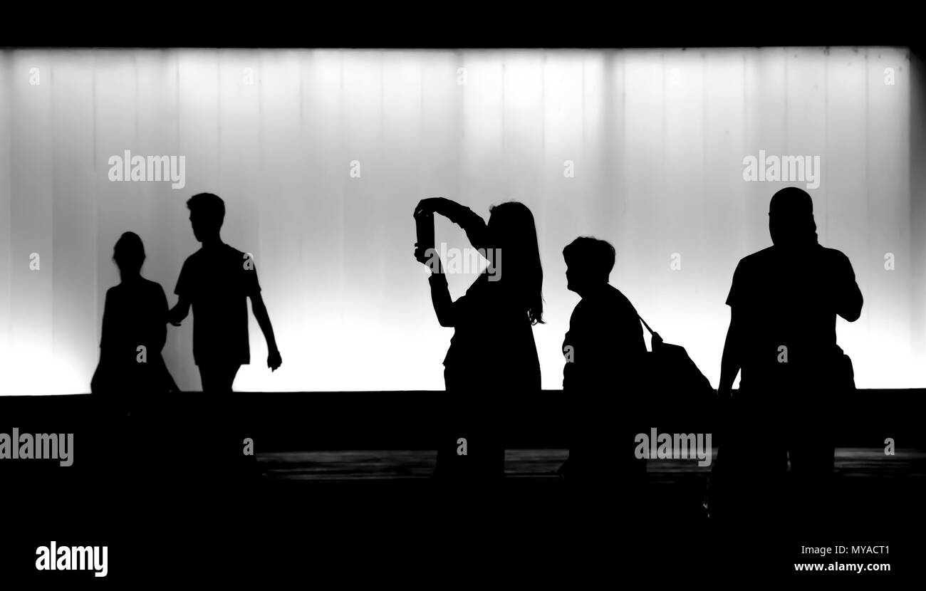 Silhouettes of  people walking in the night and a young woman making photograph on a mobile phone - Stock Image