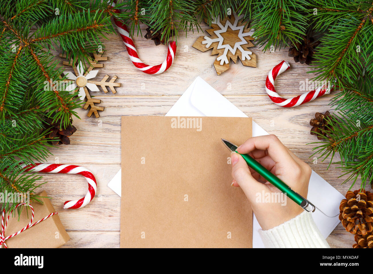 Girl Hand Writing Christmas Letter On Craft Paper With Decorations