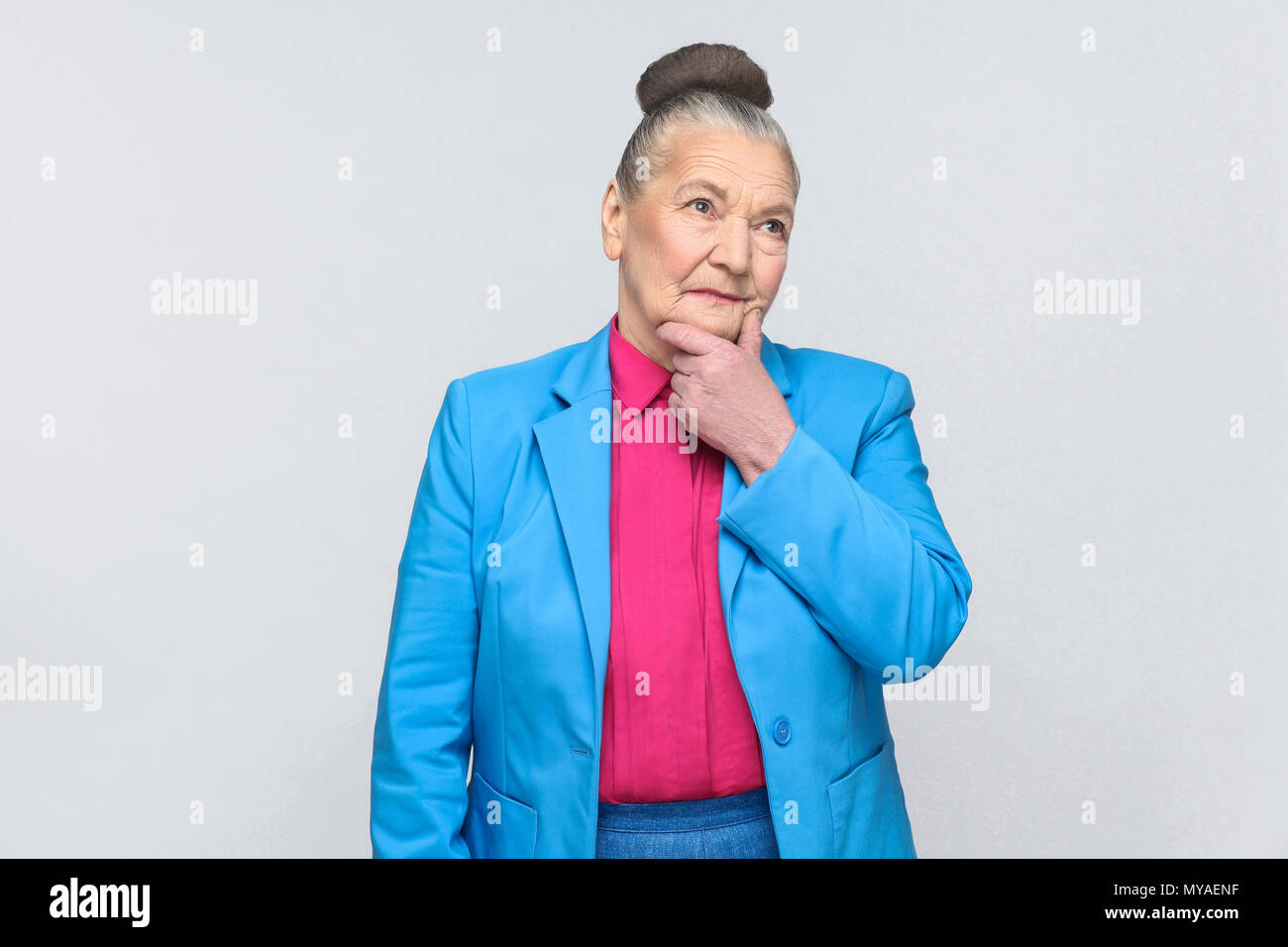 Puzzled woman thinking and touching chin. Emotion and feelings expressive grandmother with light blue suit and pink shirt standing with bun gray hairs Stock Photo