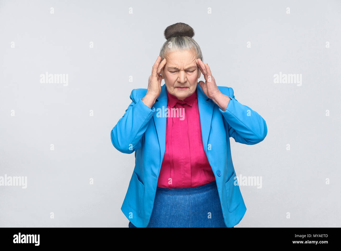 Aged woman have migraine and headache pain. Portrai of expressive grandmother with light blue suit and pink shirt standing with collected bun gray hai - Stock Image