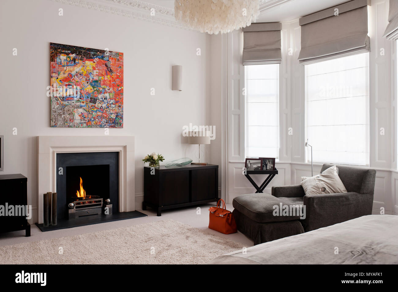 Armchair and fireplace in contemporary bedroom - Stock Image