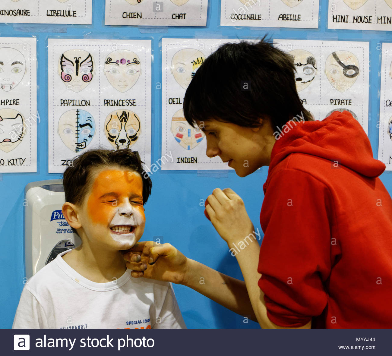 A young boy (6 yr old) grimaces while being face painted - Stock Image