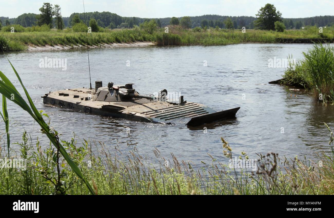 Troops in a Polish BWP-1 Amphibious Tracked Infantry Fighting Vehicle navigate a water obstacle during Saber Strike 18 in Wierzbiny, Poland, on June 04, 2018, June 4, 2018. Saber Strike 2018 is the eighth iteration of the longstanding U.S. Army Europe-led cooperative exercise designed to enhance interoperability among allies and regional partners. (Michigan Army National Guard photo by Capt. Tyler Piper/released). () - Stock Image