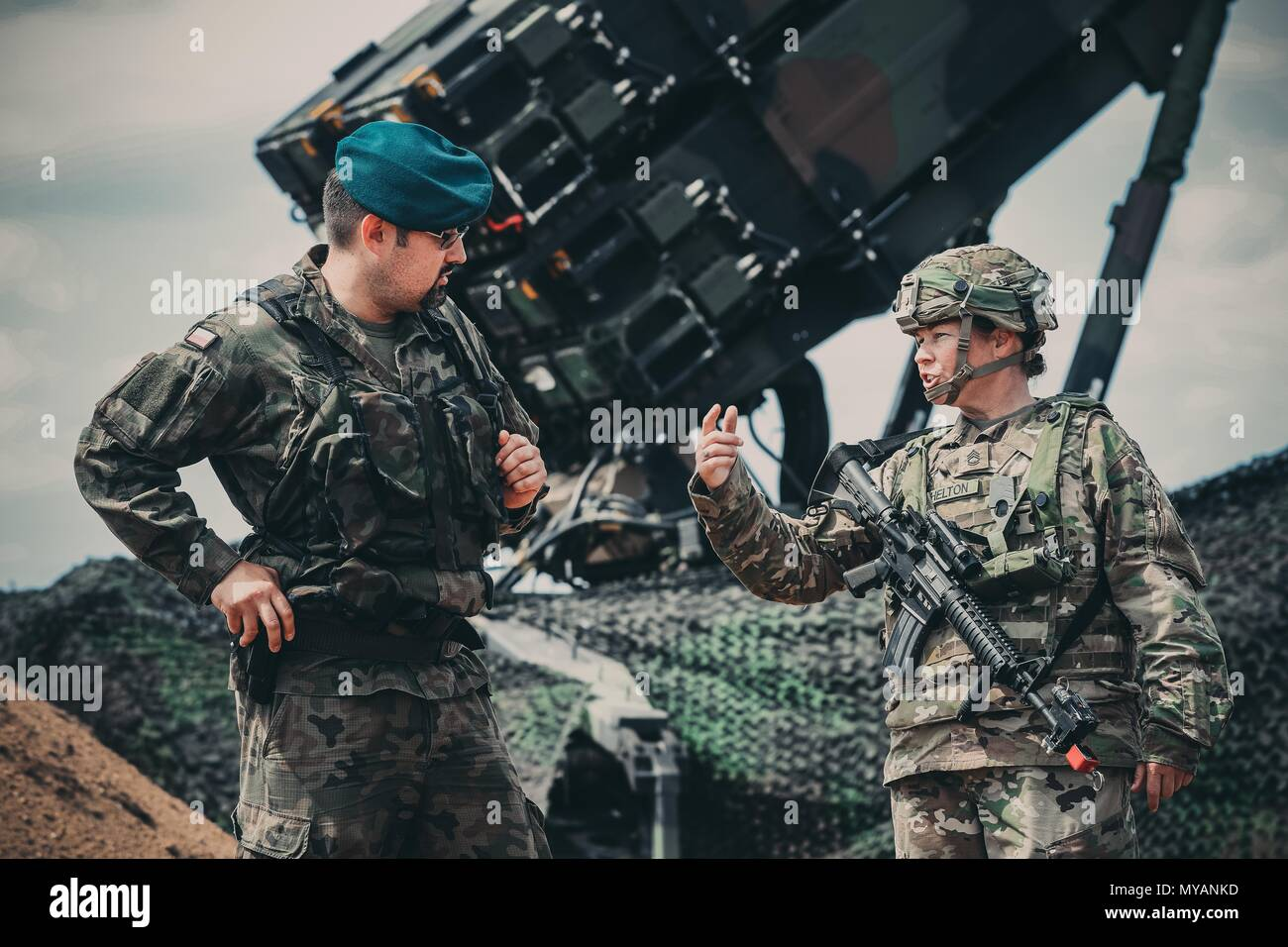 Cpt, June 4, 2018. Grzegorz Piskiewcz, the air defense officer, 12th Mechanized Division Headquarters, and Sgt. 1st Class Paige Shelton from the 5th Battalion, 7th Air Defense Artillery Regiment, discuss some of the capabilities of the new U.S. Army patriot missile system in the Drawsko Pomorskie area of Poland, June 4, 2018. Educating our allies on our defense strategies and weapon systems builds confidence among our multinational partners across the globe. (Michigan Army National Guard photo by Spc. Aaron Good/Released). () - Stock Image