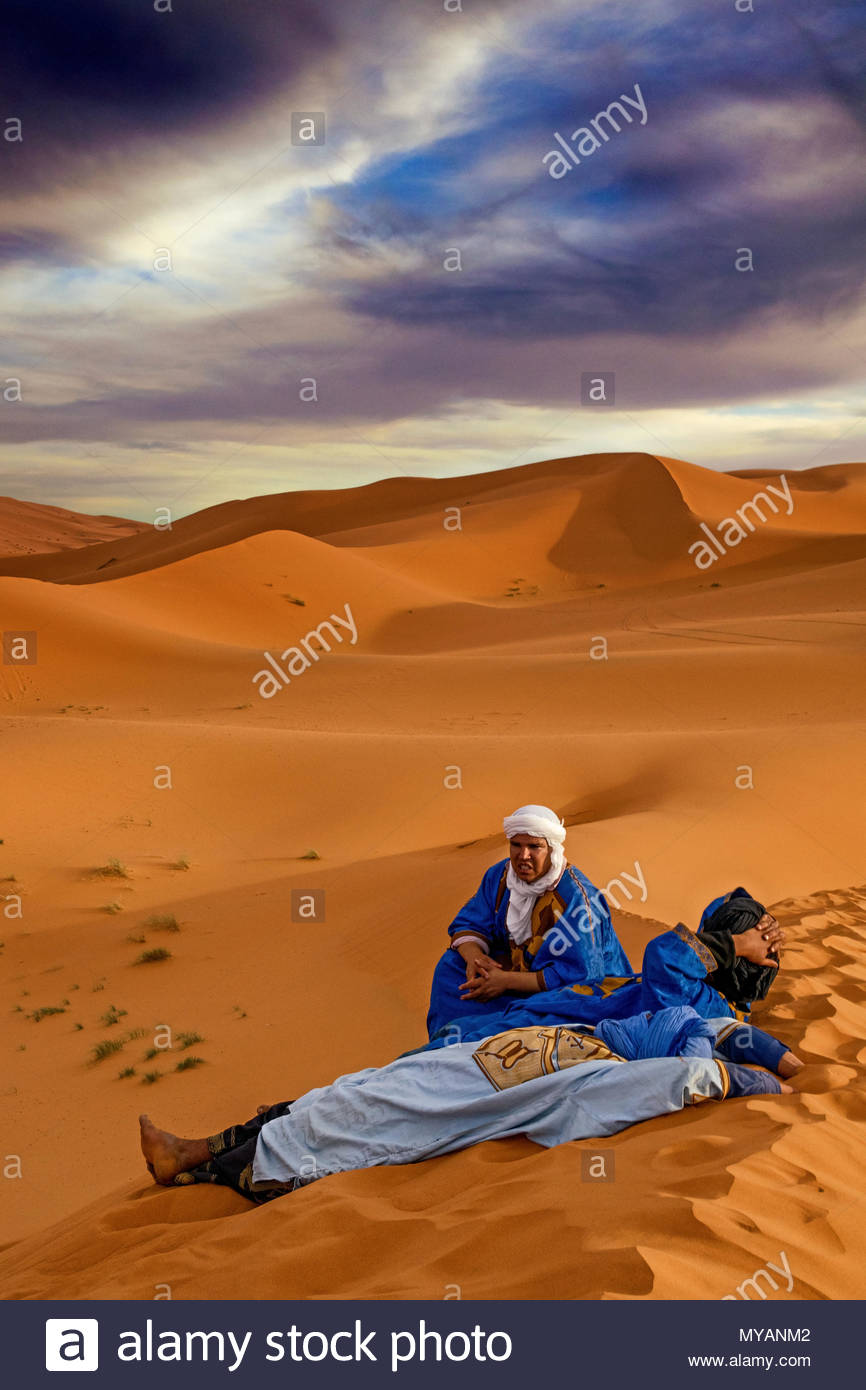 Camel Drivers Relaxing in the Sahara Desert Morocco - Stock Image