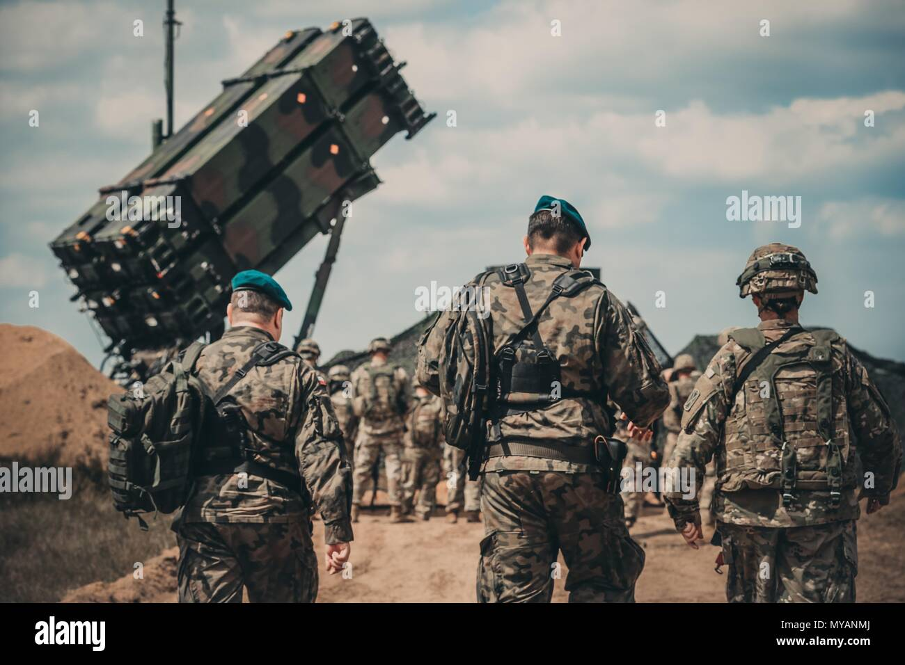 Service members from the U.S. Army and the Polish Land Forces walk to the site of the new Patriot missile system for a verbal demonstration of its operation and capabilities near Drawsko Pomorskie, Poland, June 4, 2018, June 4, 2018. Demonstrations and instructions such as these act as a show of force to our allies which instills confidence and dedication to service. (Michigan Army National Guard photo by Spc. Aaron Good/Released). () - Stock Image