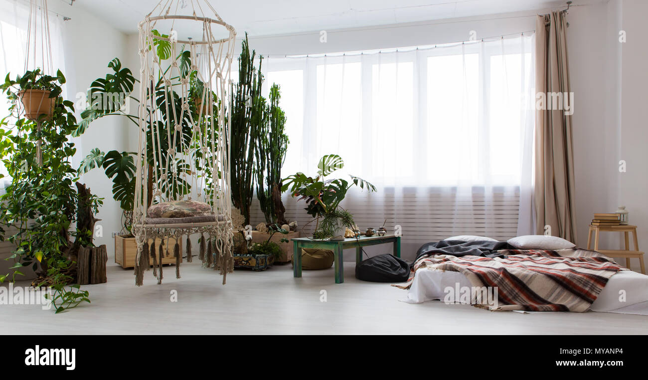 interior of a modern studio apartment with lots of plants and a bed ...