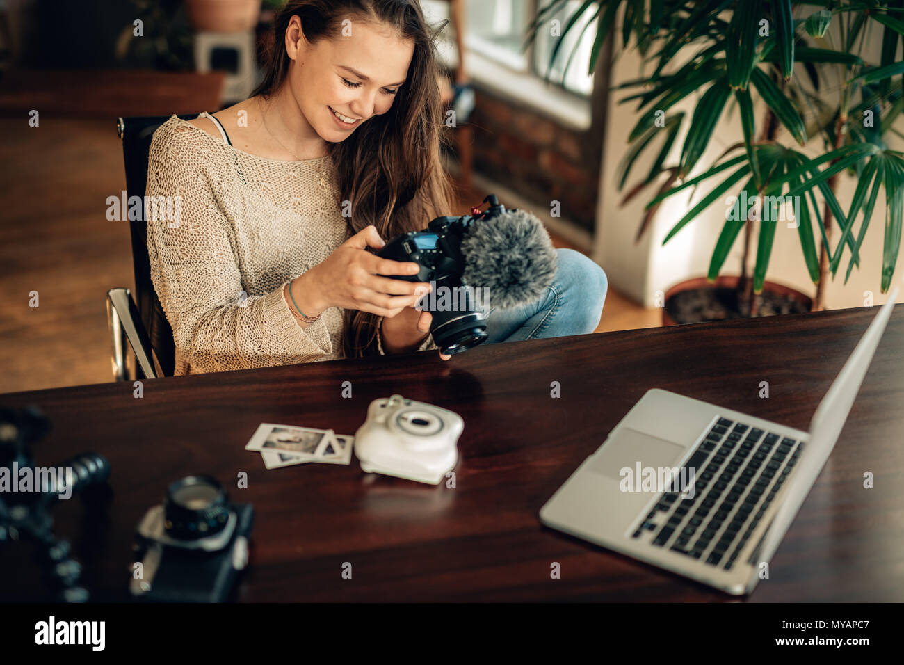 Woman blogger viewing her recorded content on camera with laptop and cameras on the table. Blogger reviewing the recorded content for her blog sitting - Stock Image