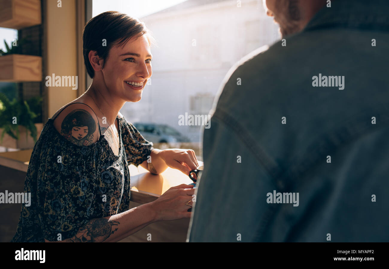 Beautiful woman sitting at a cafe table with her boyfriend.  Smiling young couple at coffee shop. - Stock Image