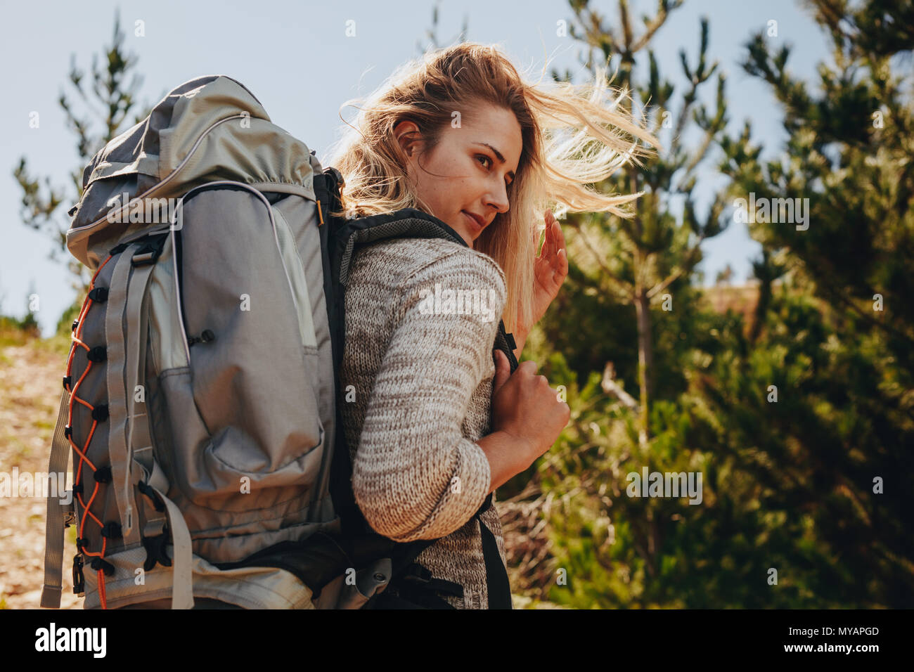 Woman with backpack on hike in nature. Female hiker on mountain trail and looking at a view. - Stock Image