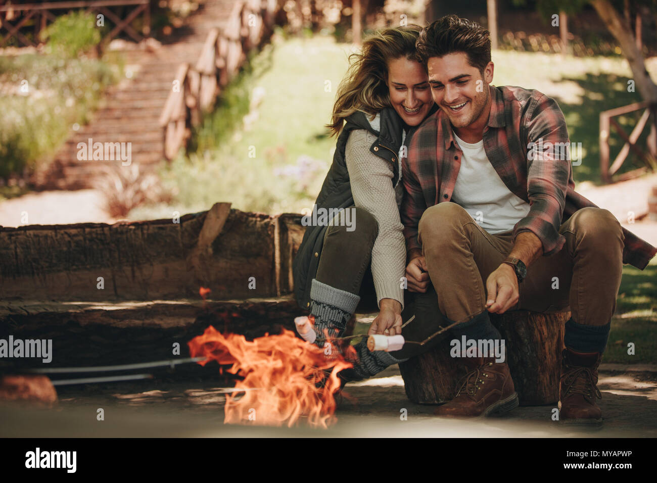 Smiling young couple roasting sweets on bonfire at campsite. Man and woman having roasted marshmallows on camping. - Stock Image