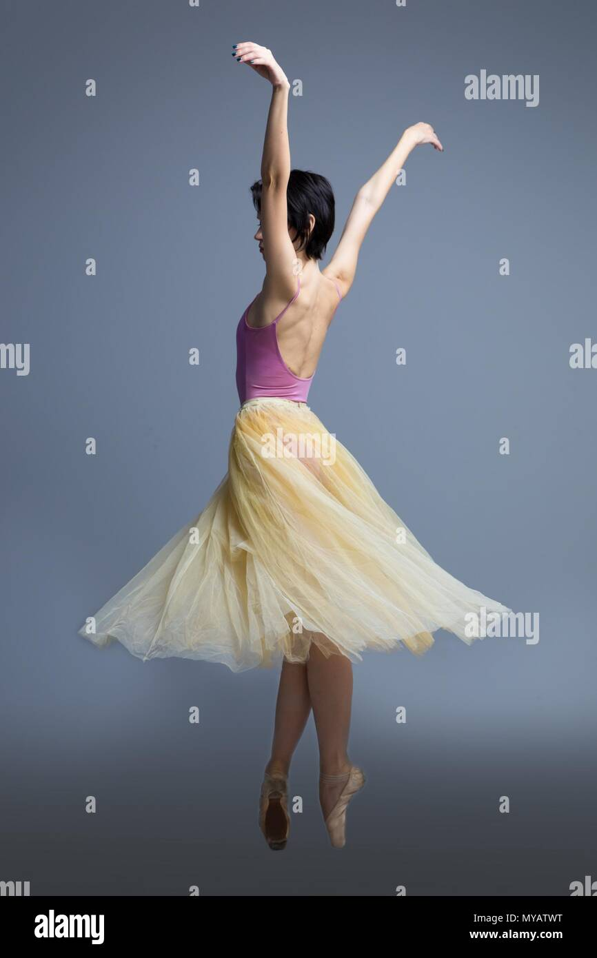 ballerina is dancing in the studio on a gray background  Stock Photo