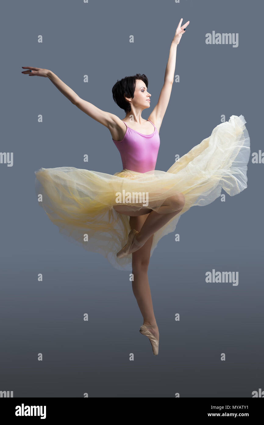 ballerina is dancing in the studio on a gray background  - Stock Image