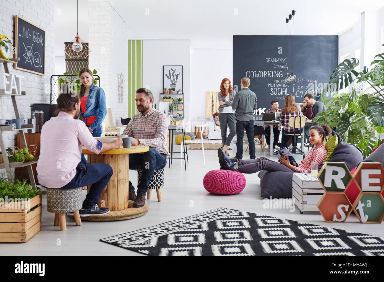 People working in modern agency relaxing during lunch break - Stock Image