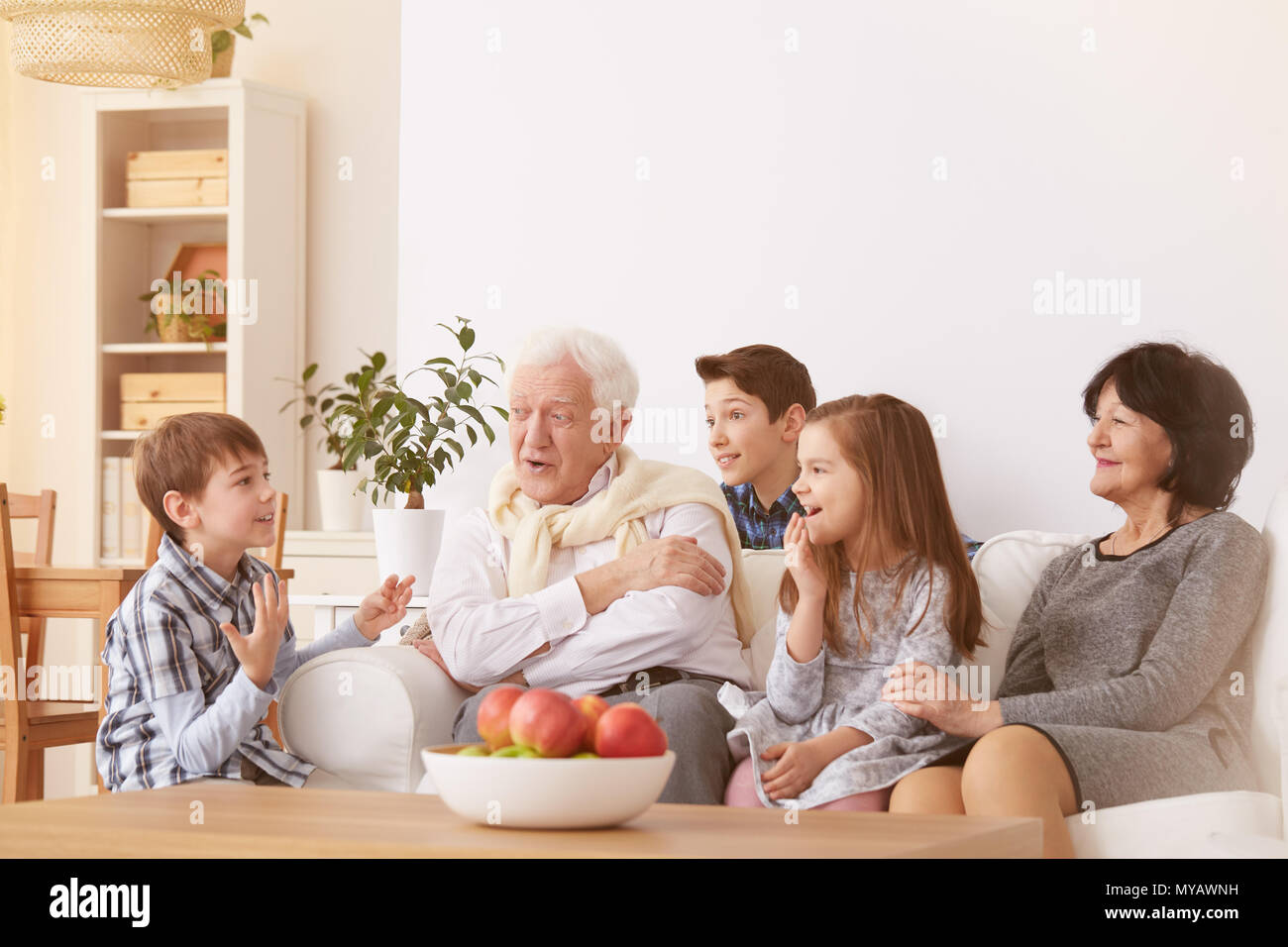 Happy children spending time with grandparents in living
