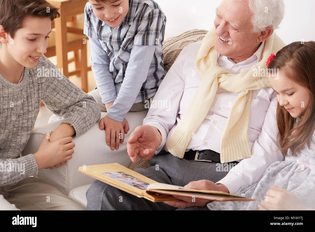 Happy children sitting on sofa with grandpa holding a photo album - Stock Image
