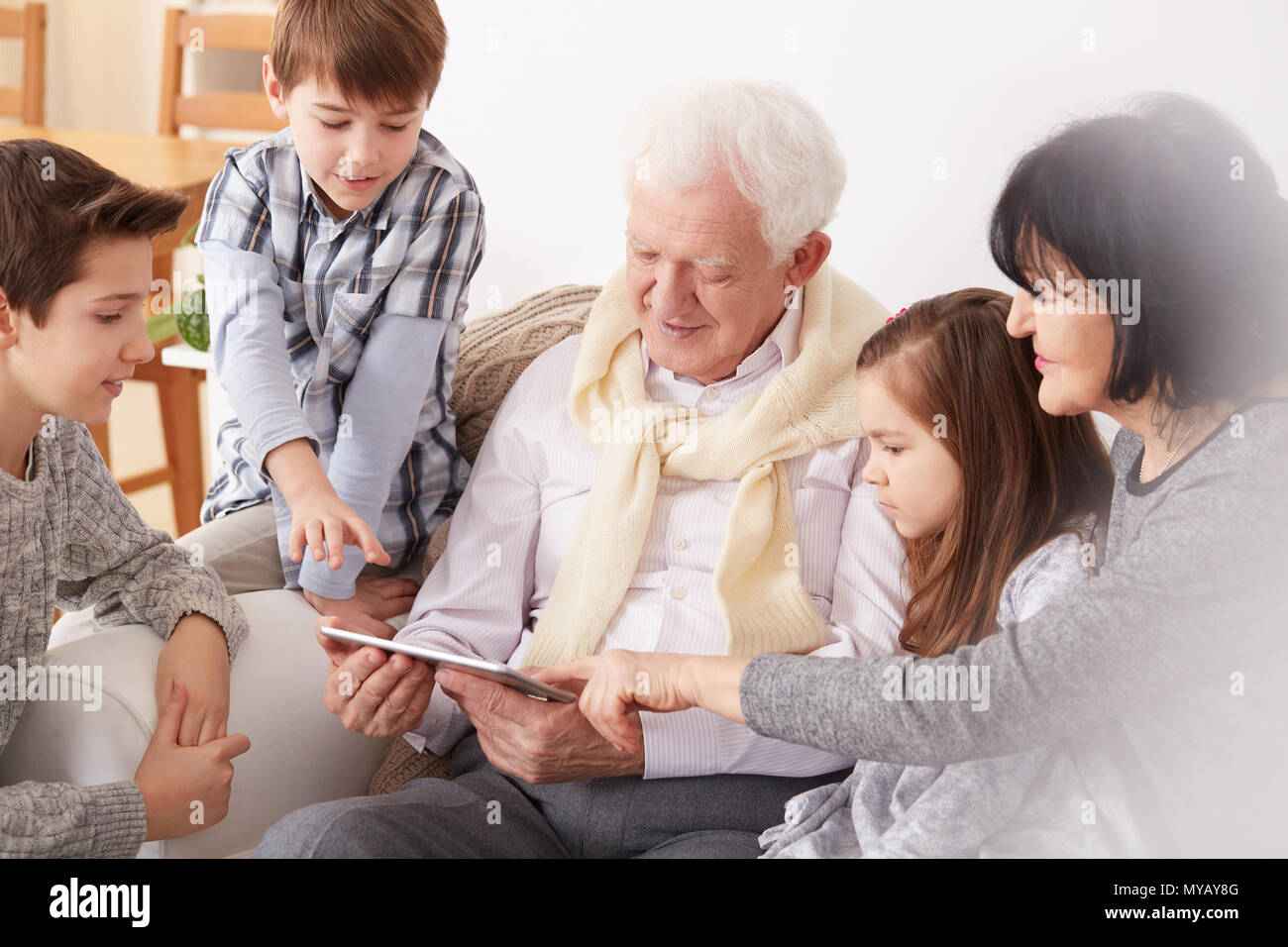 Grandchildren teaching grandpa how to use tablet - Stock Image