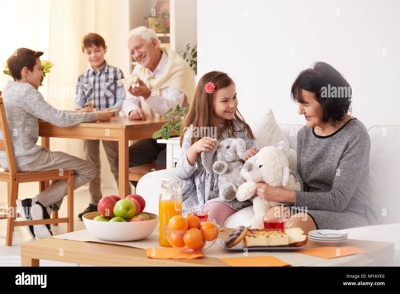 Happy granddaughter showing her toys to grandma in living room - Stock Image