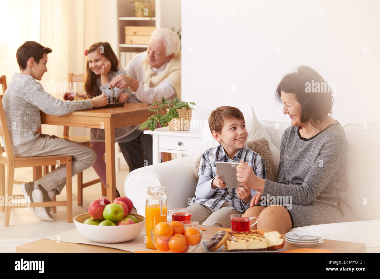 Happy grandchildren visiting their grandparents and spending free time with them - Stock Image