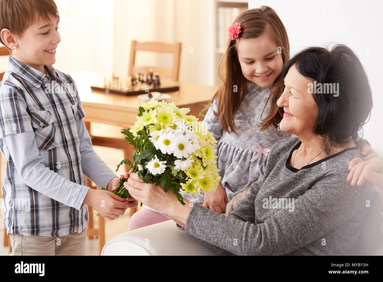 Happy grandchildren giving a bunch of flowers to their grandma sitting on a sofa - Stock Image