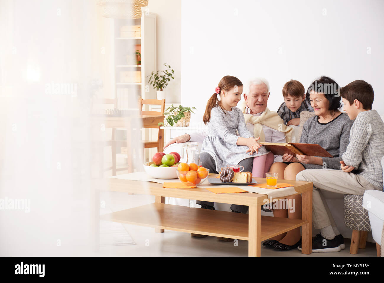 Happy grandparents showing photo album to their grandchildren in a living room - Stock Image