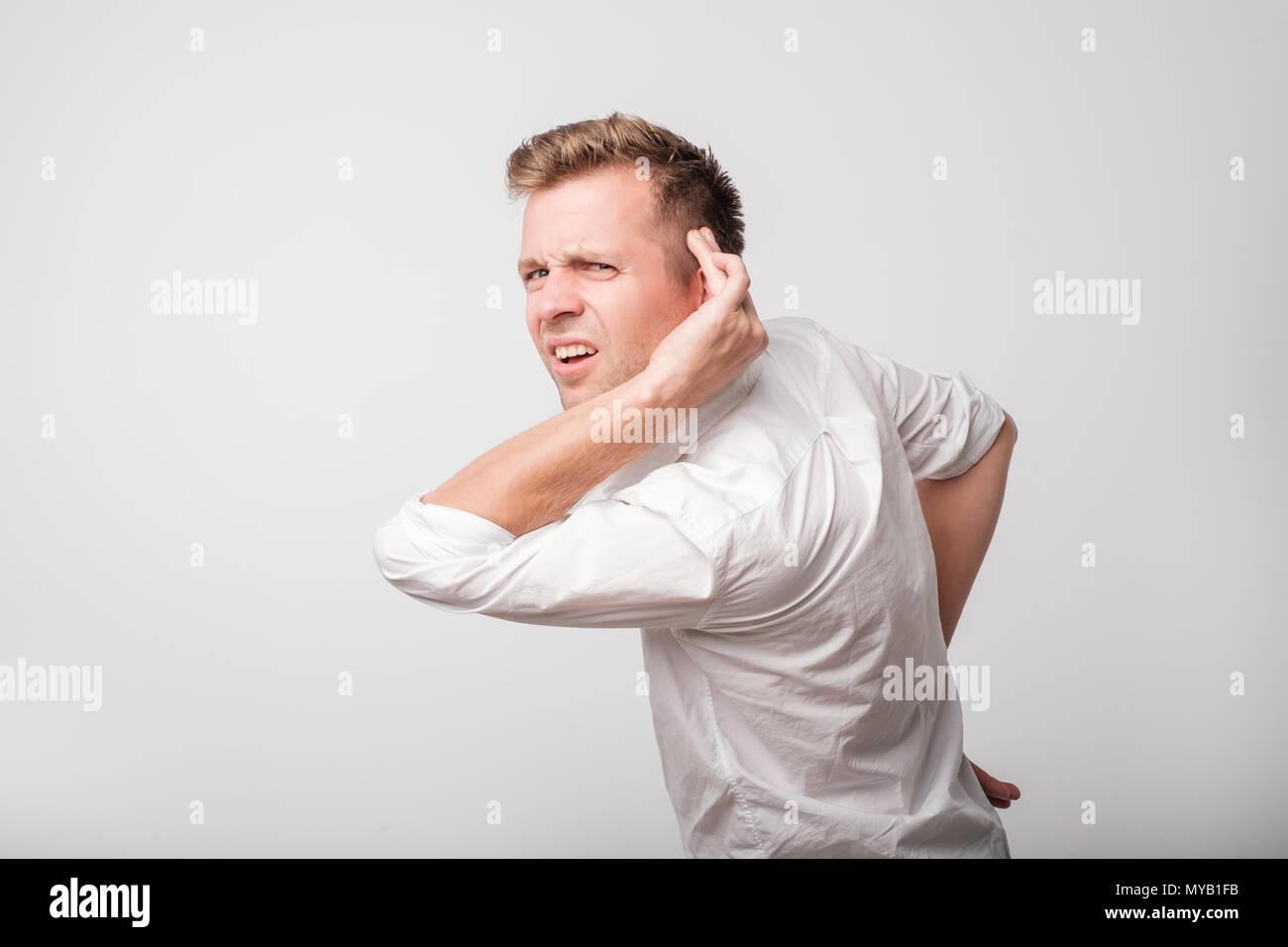 Caucasian man having hearing problem listening to something - Stock Image