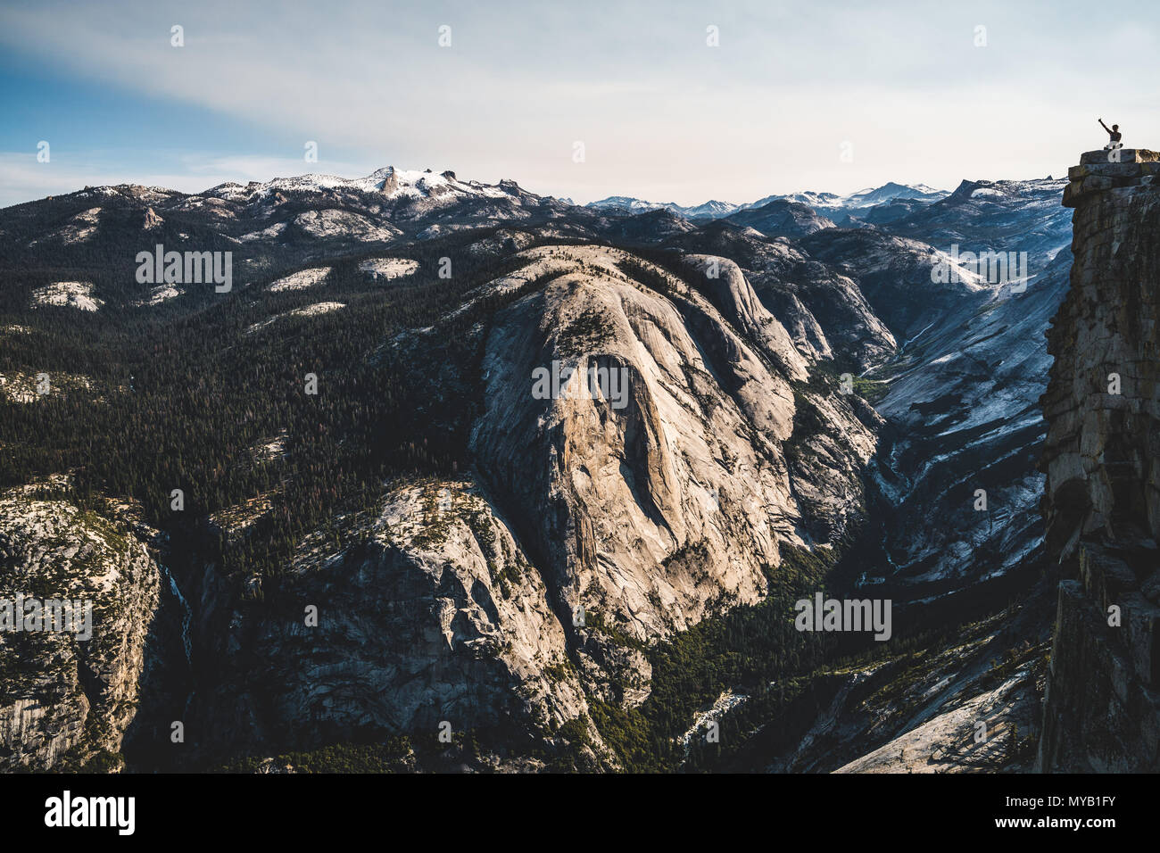 A tiny, lonely hiker on top of Half Dome in Yosemite National Park. - Stock Image