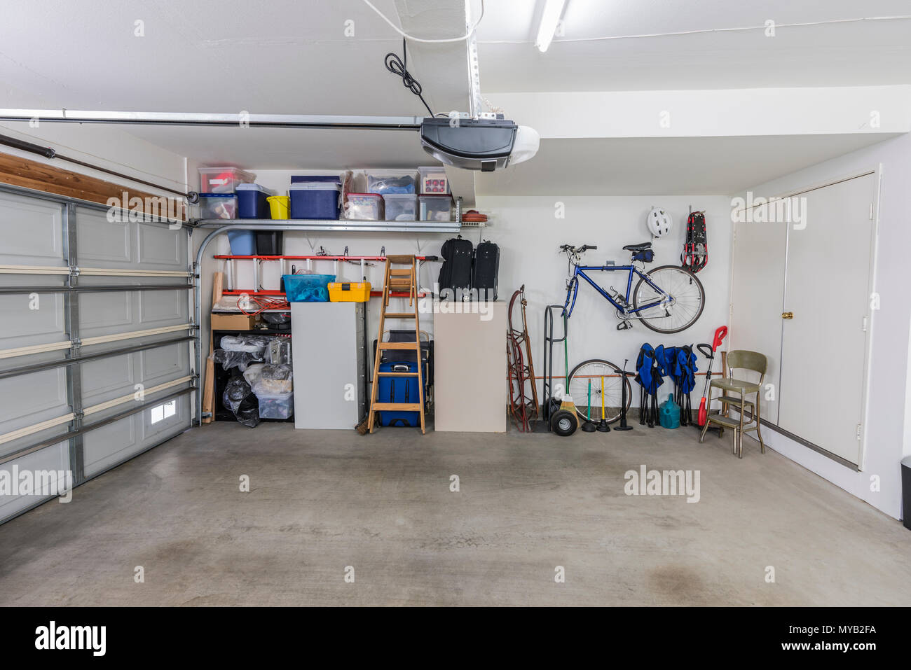 Organized clean suburban residential two car garage with tools, file cabinets and sports equipment. - Stock Image