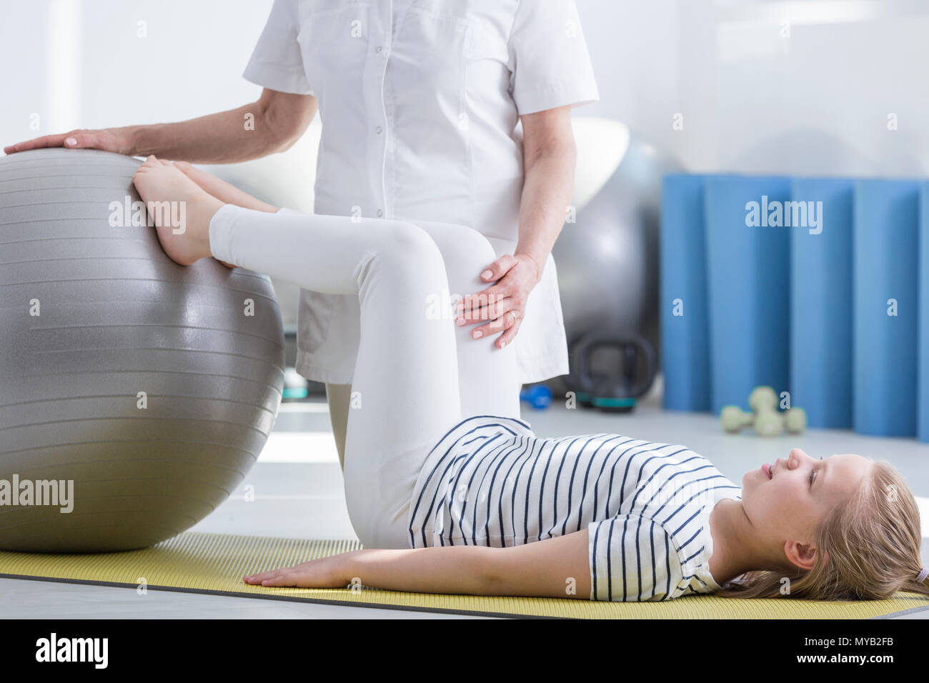 Little girl with scoliosis working with gym ball  doctor - Stock Image