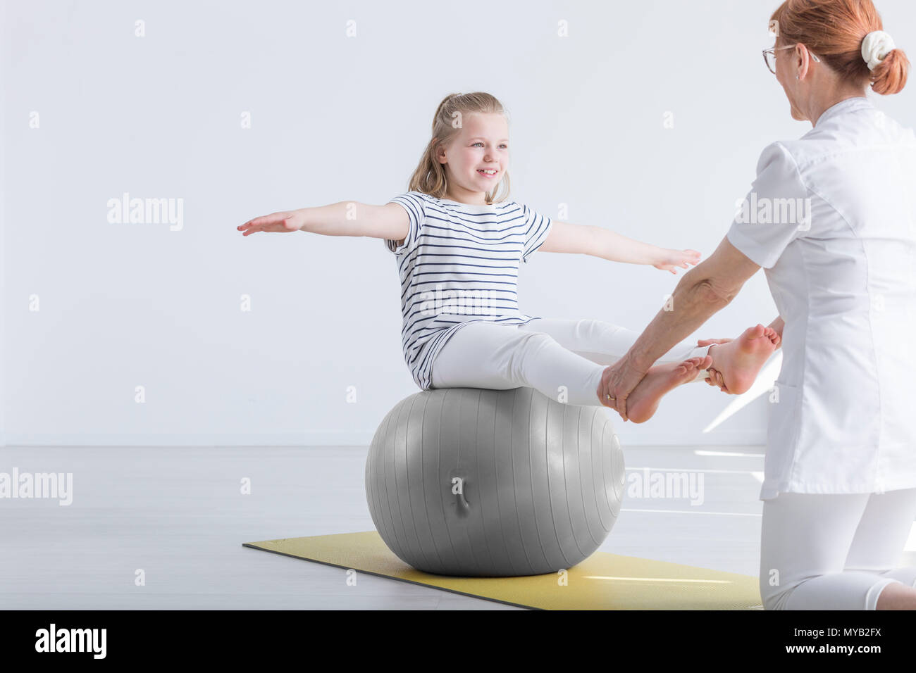 Smiling girl sitting on big gym ball working with physiotherapist - Stock Image