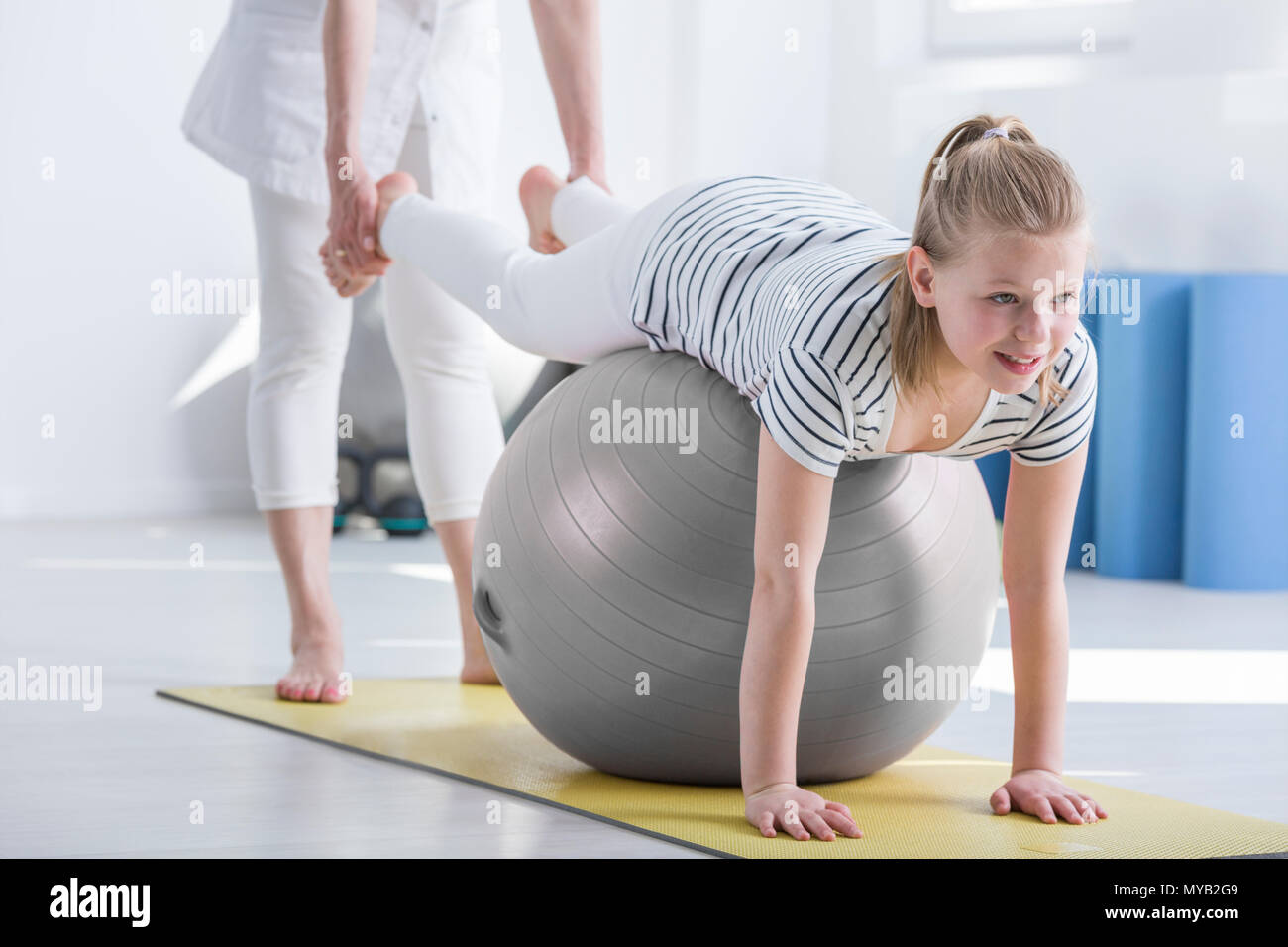Smiling young girl lying on ball during pediatric occupational therapy - Stock Image