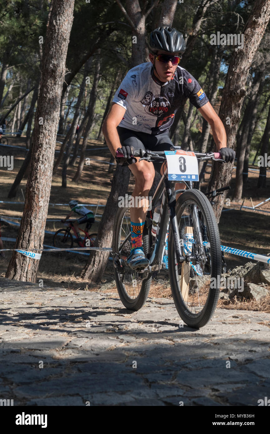 Greek male cyclist competes in an international mountain bike race in the forest course outside the Greek village of Molyvos on the island of Lesvos - Stock Image