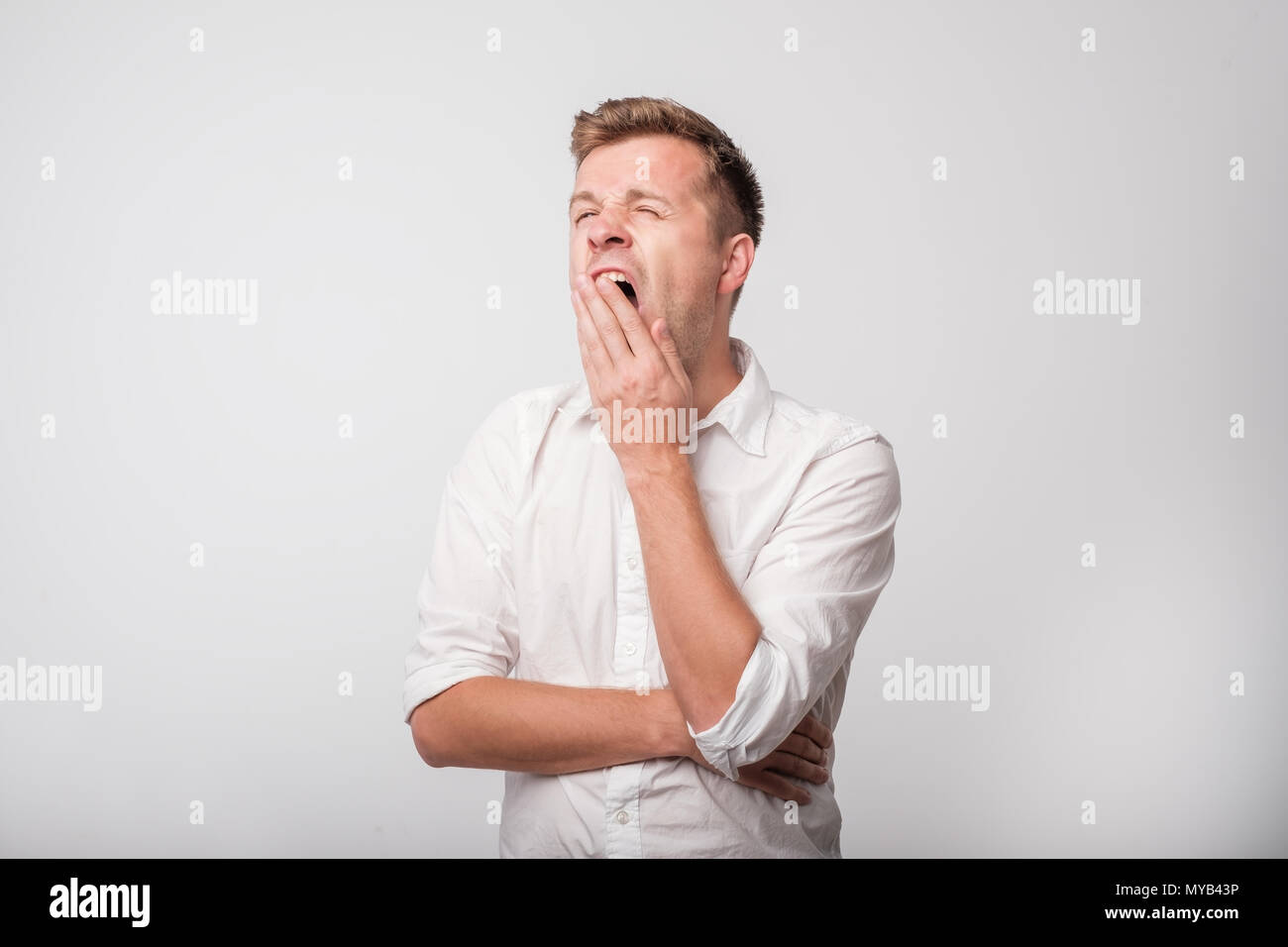 Portrait of caucasian yawning man. - Stock Image
