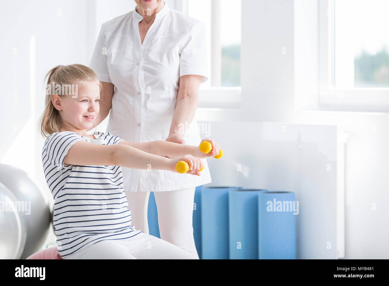 Physiotherapist and child exercising with yellow dumbbells in rehabilitation room - Stock Image
