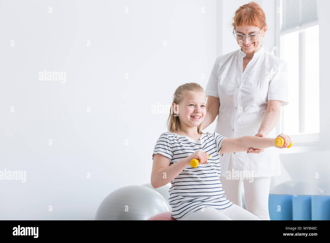 Photo of kid exercising with dumbbells with copy space - Stock Image