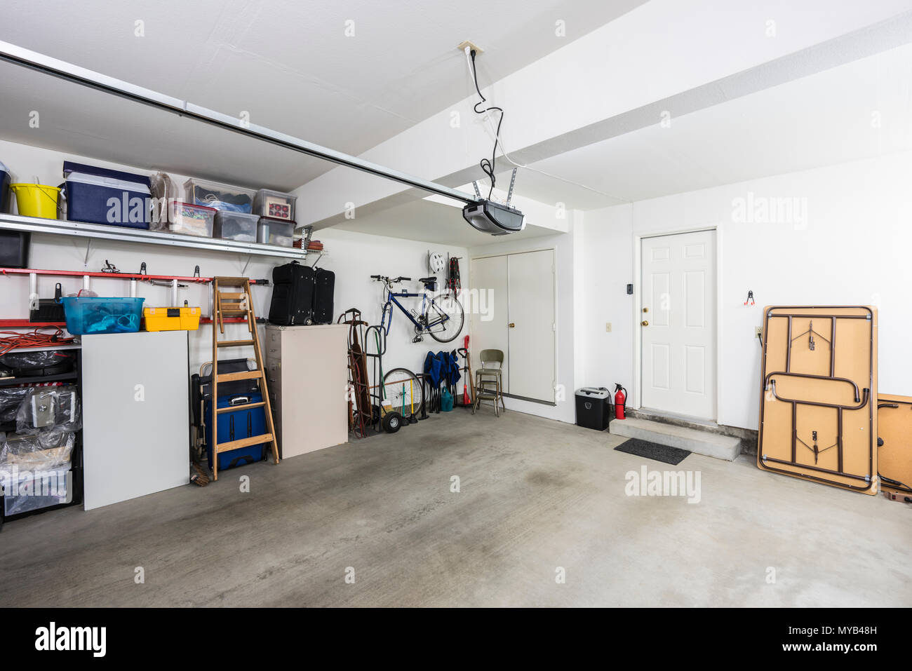 Clean organized suburban residential two car garage with tools, file cabinets and sports equipment. - Stock Image