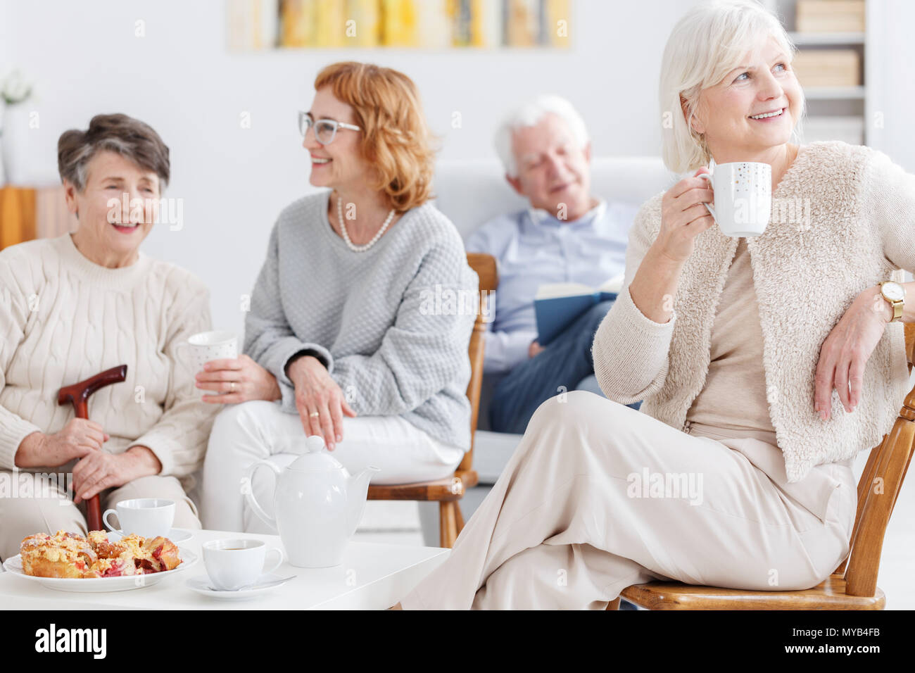 Elderly woman on her coffee time with friends in senior club - Stock Image