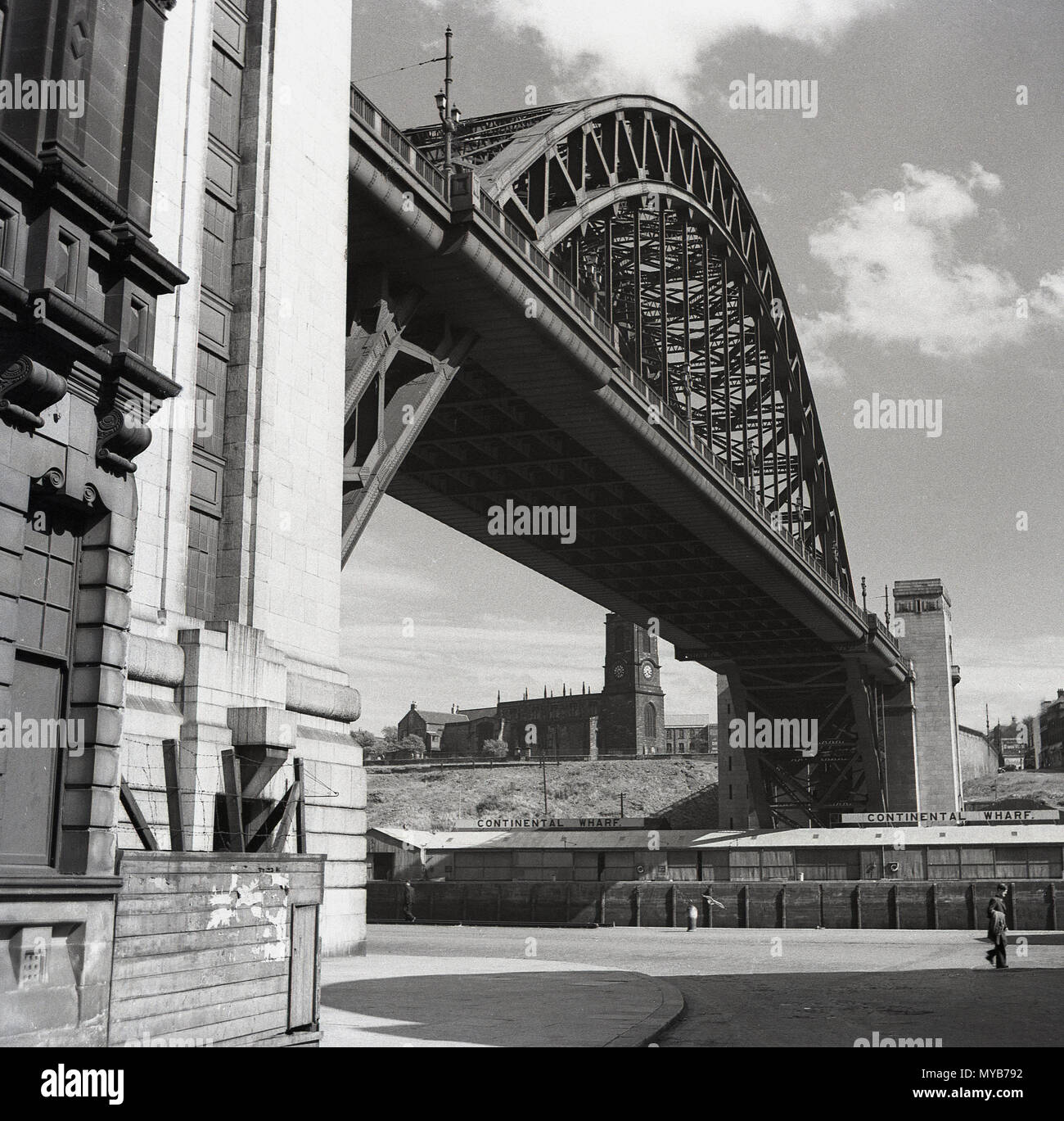 1950s, historical picture, a view from below, from the quayside of the Tyne Bridge, a gthrough arch bridge over the River Tyne, linking the city of Newcastle to the town of Gateshead, England, UK. it was the biggest single-span bridge in the UK when officially opened by King George V in October 1928. - Stock Image