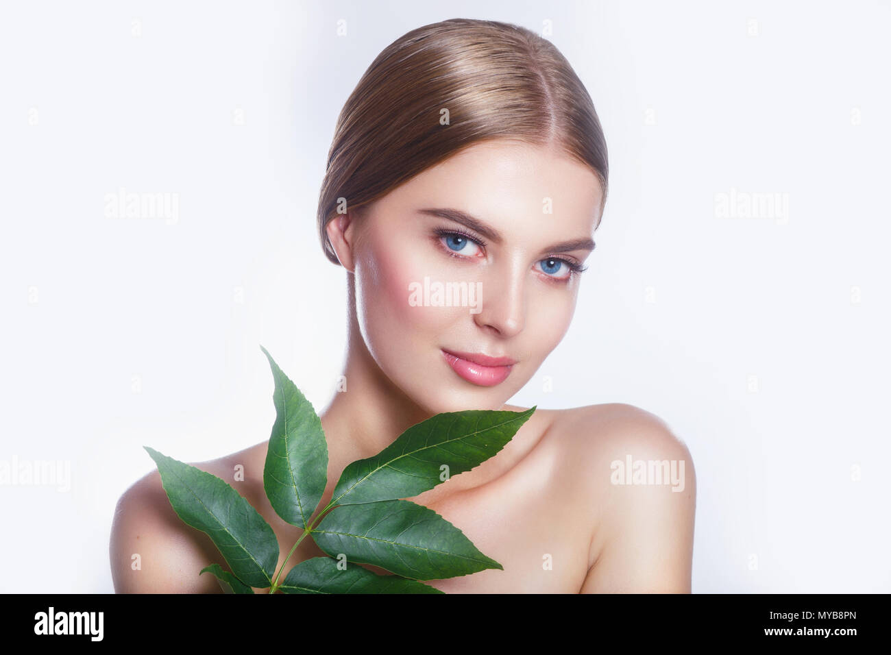 Beautiful woman face portrait with green leaf concept for skin care or organic cosmetics Stock Photo