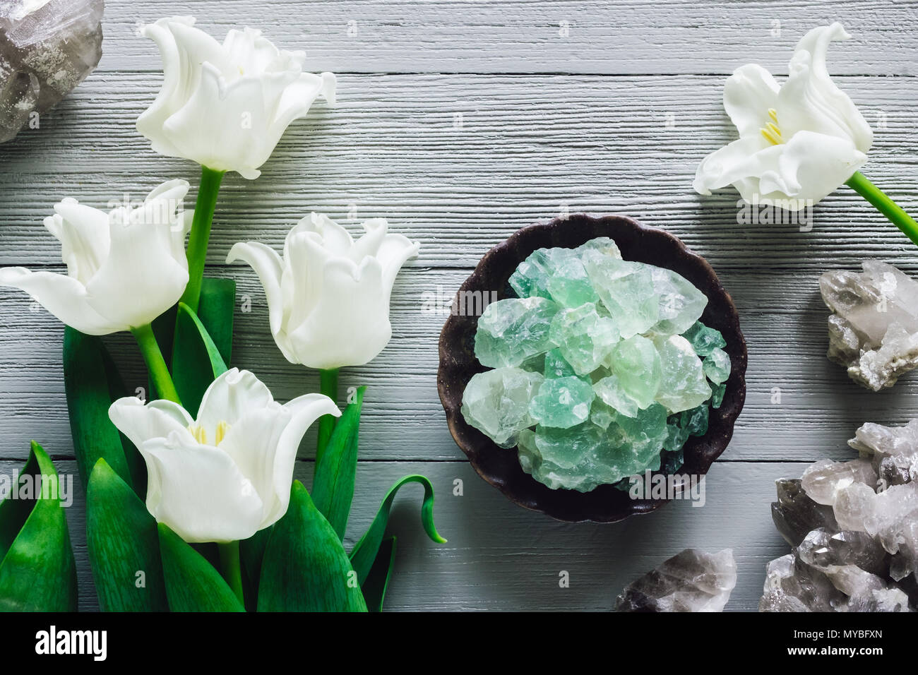 White Tulips with Quartz and Fluorite Crystals on Grey Table - Stock Image
