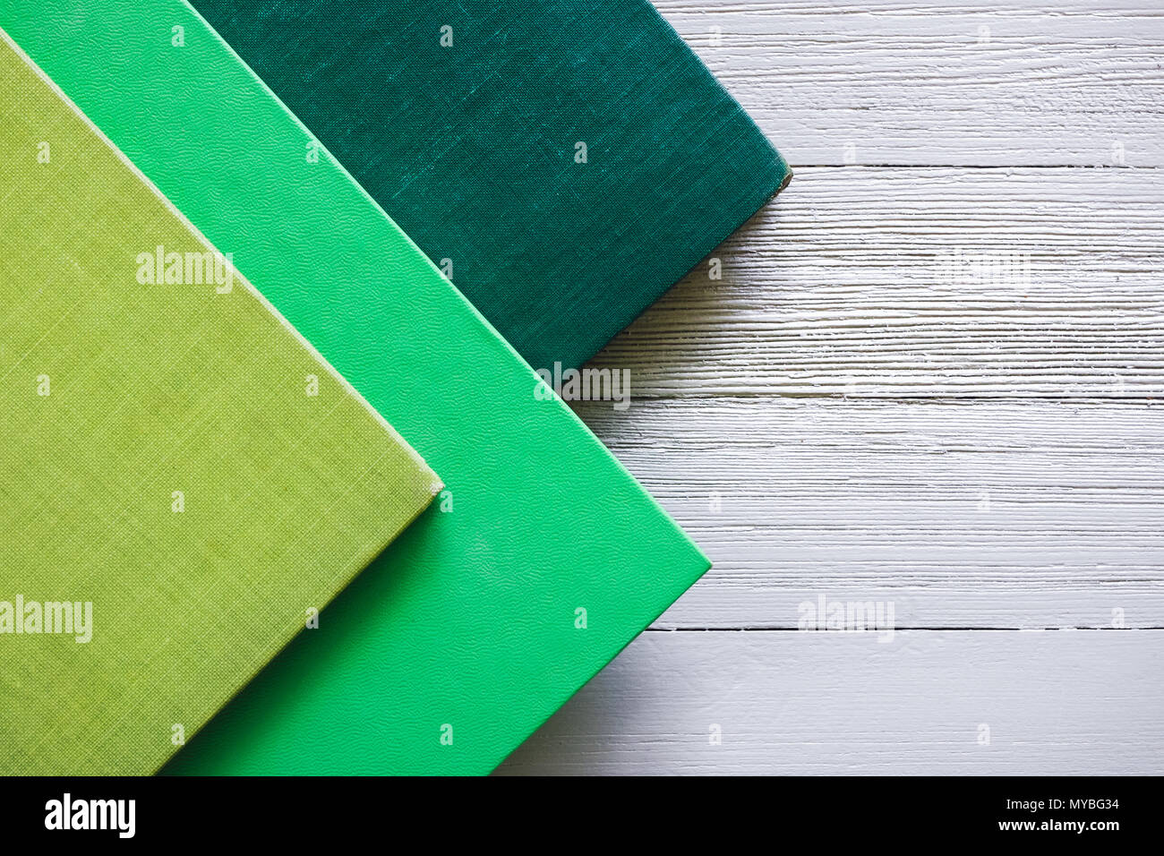 Stacked Green Covered Books on White Table with Space for Copy - Stock Image