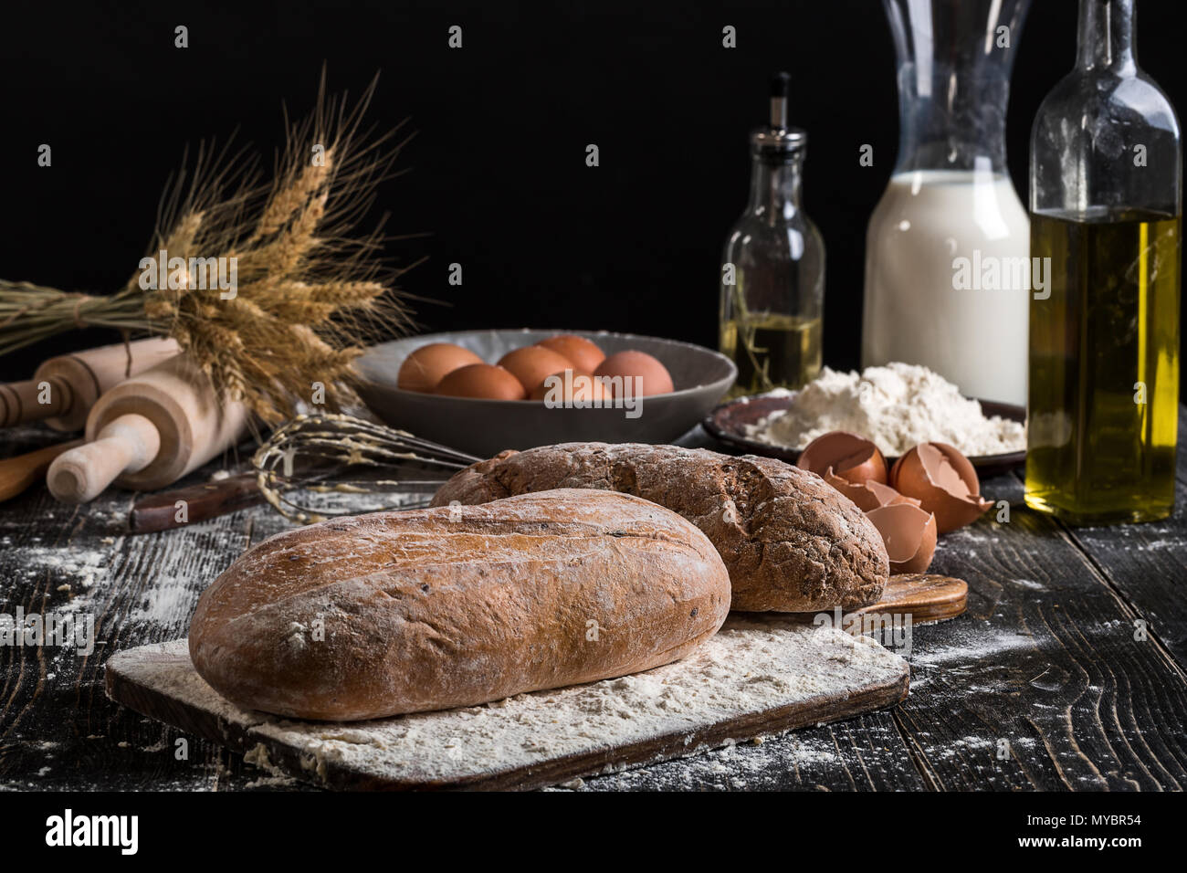 Beautiful still life with different kinds of bread, grain, flour on weight, ears of wheat, pitcher of milk and eggs - Stock Image