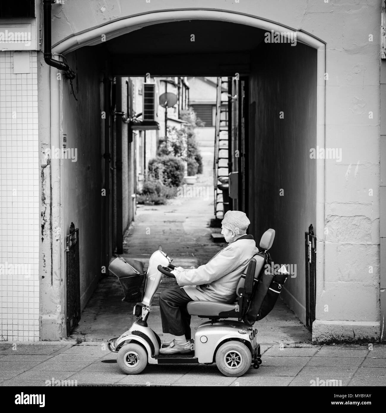 Elderly man on a disability scooter in the Scottish Highland Town of Nairn, UK - Stock Image