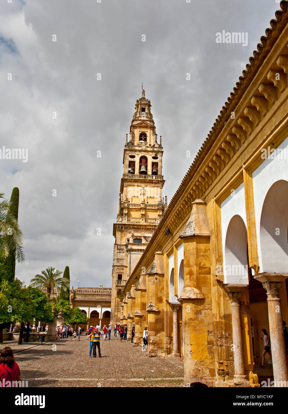 May 28, 2016- Cordoba, Spain: the landmark bell tower at the cathedral mosque in spanish cordoba with tourists in courtyard Stock Photo