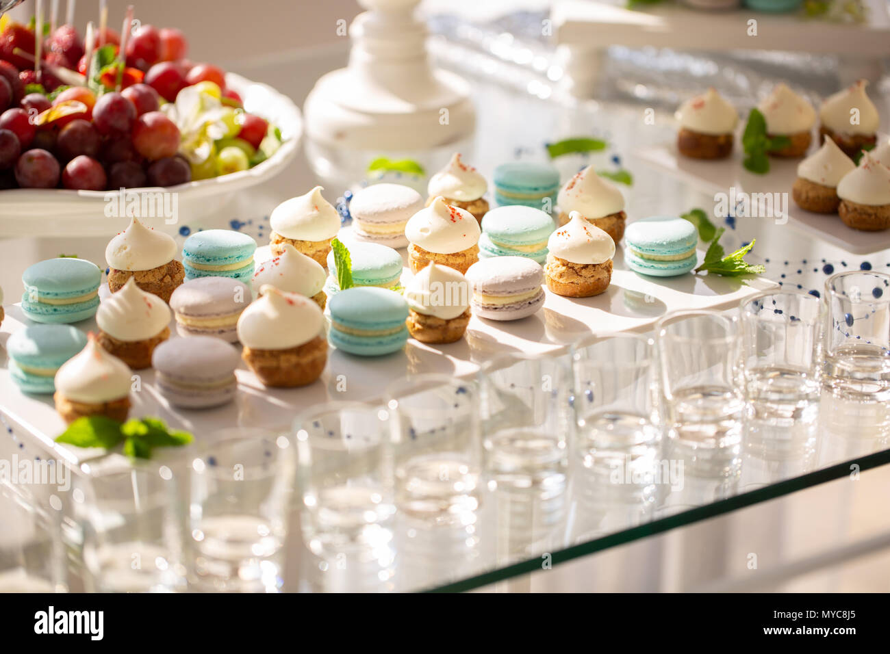 Delicious Macaroons And Cupcakes On Table At Wedding Reception